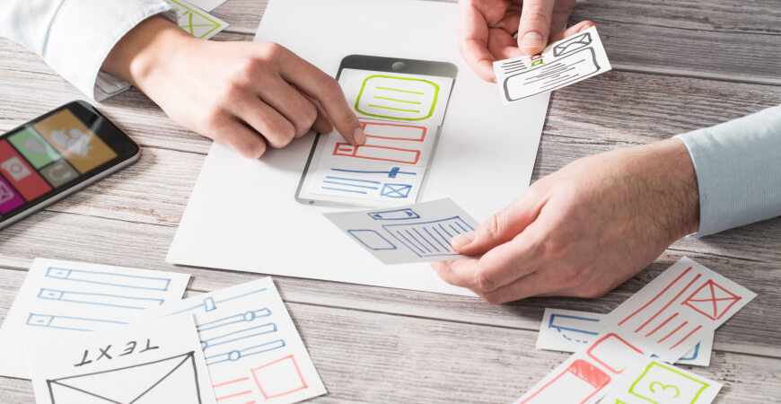 Close up of two designers holding pieces of cut paper with sketches of website layouts above a print-out of a smartphone on a light gray wood desk.