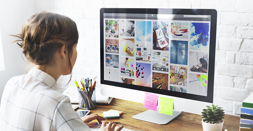 Woman designer wearing business attire sitting at a desk with pencils, a smartphone, sticky notes, plant, books, and a desktop computer screen displaying a gallery filled with vibrant images.