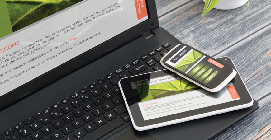 Close up of a laptop computer sitting on a gray wooden table with a tablet and phone sitting on its keyboard, all featuring the same responsive website.