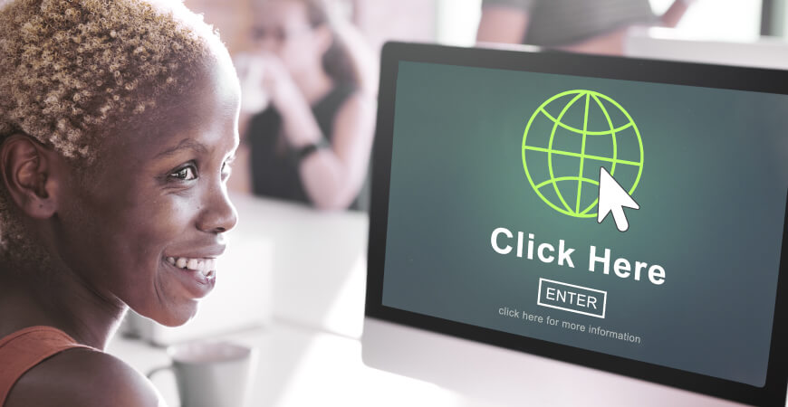 "Smiling woman sitting at a desk with people blurred in the background, looking to her right, in front of a desktop computer that has a screen that reads ""Click Here, Enter, click here for more information"" with a graphics of a white mouse and green outlined globe icon."
