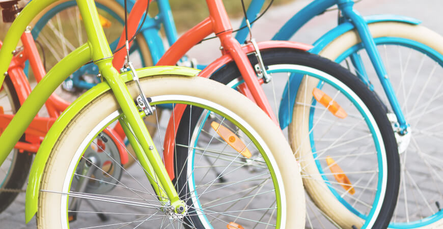 Close up of vibrant green, pink, and teal bicycles.