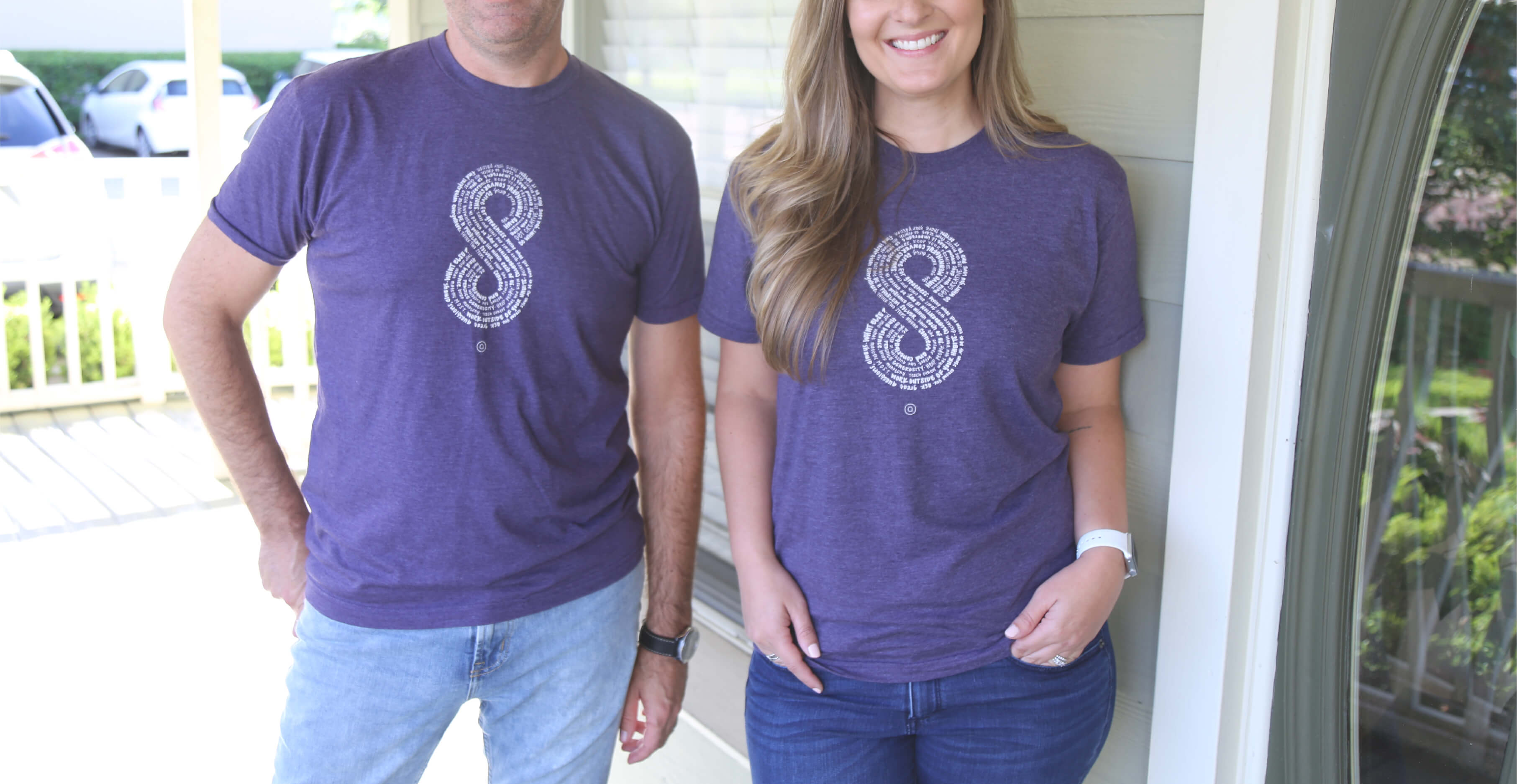 Close up of both a male and female Aedieno team member standing on a brightly lit front porch wearing purple Aedieno 8-year anniversary shirts.