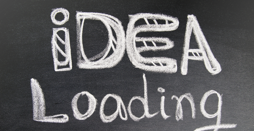 Close up of a dark gray chalkboard with decorative text in white chalk that reads: idea Loading.