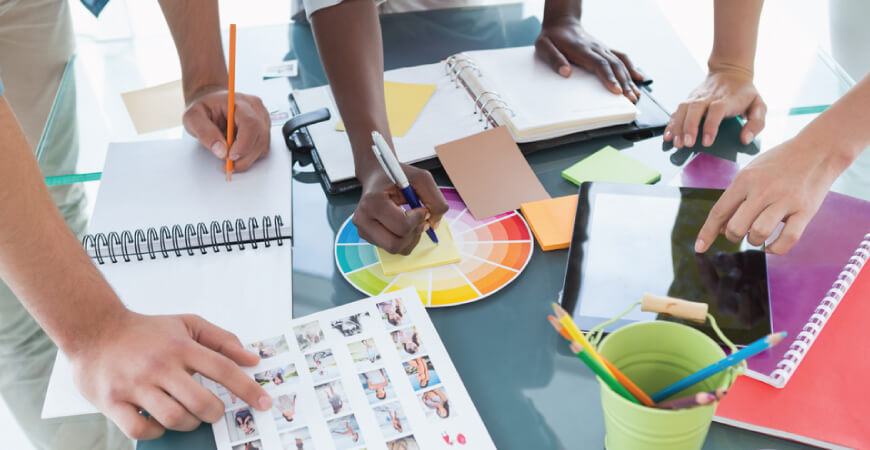 Close up of three collaborating designers standing above a table all doing different tasks with notepads, pencils a printed sheet of photo proofs, tablet, and other creative supplies on the table.