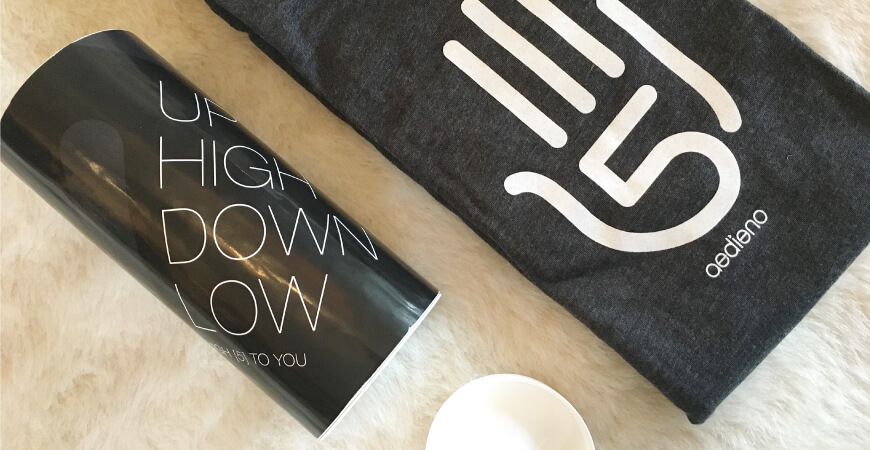 "Aedieno five year ""high-5"" anniversary shirt and accompanying cylindrical packaging featuring copy that reads, ""Up High Down Low."""
