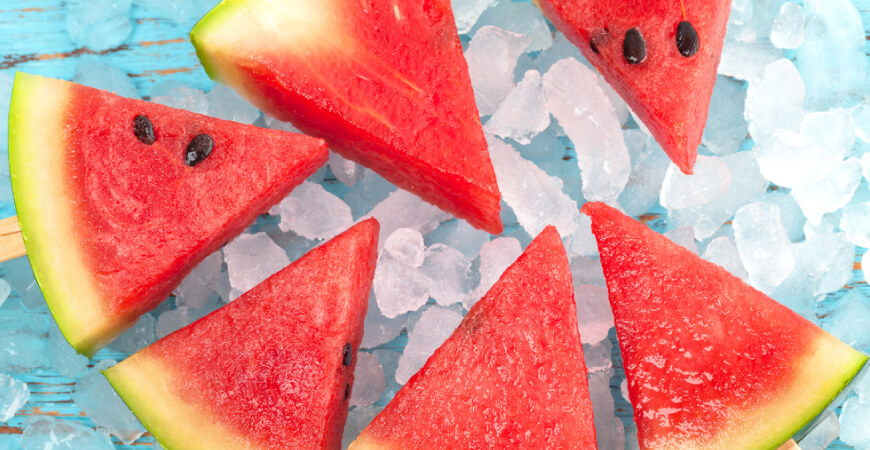 Close up of six watermelon slices sitting on ice on a blue wooden table.