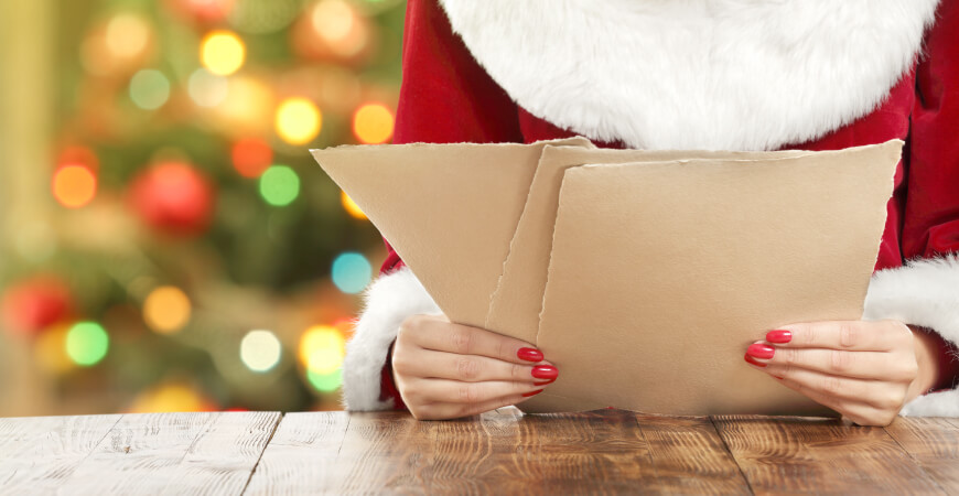 Close up of a woman wearing a Santa outfit with painted red nails sitting at a wood table holding three sheets of brown paper that have torn edges, with a blurred Christmas tree with lights in the background.