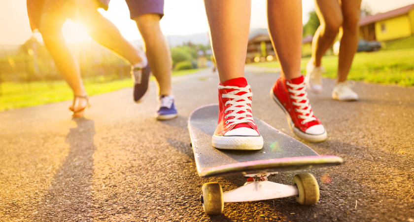 Close up of the feet of three people running along a road at sunset, all wearing sneakers, with a person at the front skateboarding and wearing bright red high-tops.