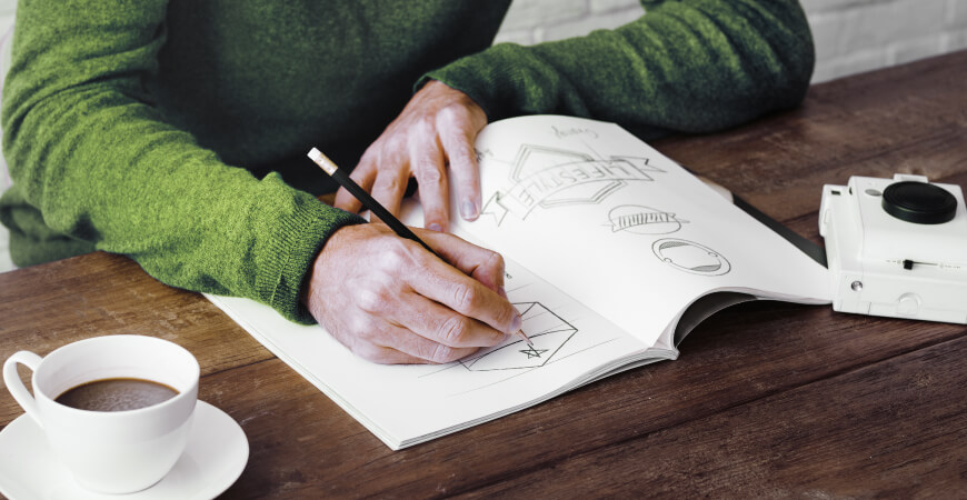 Close up of a male graphic designer wearing a green sweater sketching logo ideas on a notepad on a dark wooden table with a cup of coffee and small white camera.