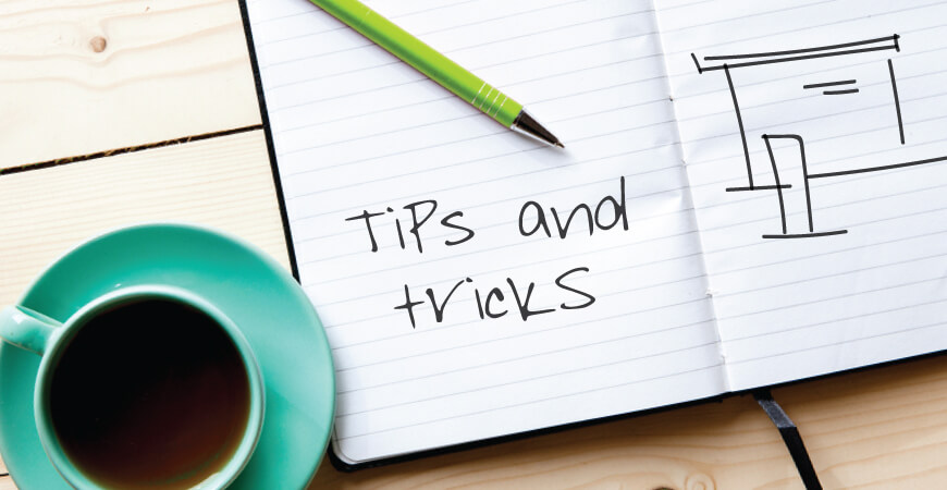 "Top view of a teal full cup of coffee next to an open notebook with a green pen and sketch that reads ""tips and tricks"" and a loose display sketch all sitting on a light wood table."