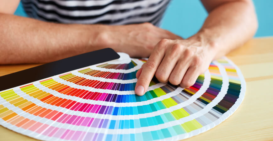 Close up of a man sitting at a wood desk pointing to a color on a fanned-out Pantone color book.