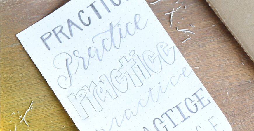 "Close up of a dotted piece of paper that has different graphic stylings of the word ""Practice"" written in pencil with paper shavings around it on a wood desk."