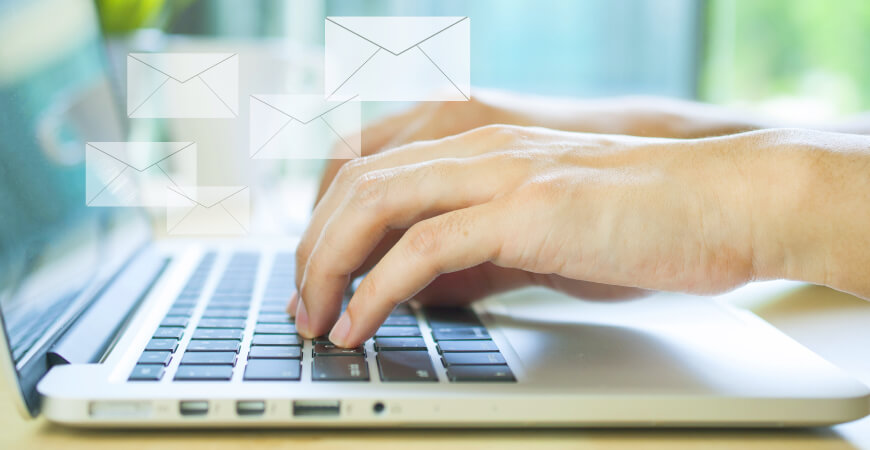 Close up side view of hands typing on a laptop computer keyboard with mail icons above the keyboard.