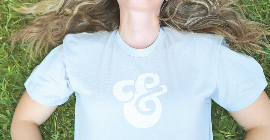 Close up of a woman with blonde, curled hair lying down in grass wearing the Aedieno 6-year light blue anniversary shirt with a white design.