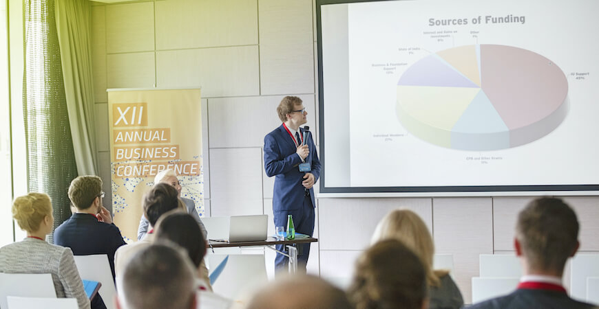 A man standing giving a presentation at a business conference looking at a screen with a pie chart, with an audience in the foreground.