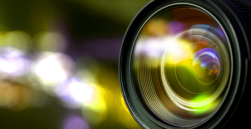 Close up of a camera lens with warm colors reflected in the glass and bokeh in the background.