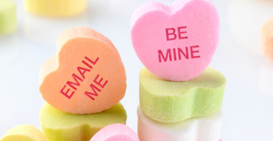 "Close up of candy hearts sitting on other candy hearts that read, ""Email Me"" and ""Be Mine"" in soft light."